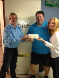 Davie Schneider presents our donation of Audrey Luce and Craig Williams, Heritage of Pride Co-Chairs